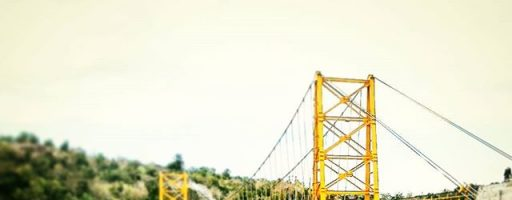 Yellow bridge. It connects Lembongan with Caningan. This suspension bridge is only made for pedestrians, bikes and scooters/motorcycles. It crosses the channel, which is dry at low tide. #yellowbridge #yellow #suspension #bridge for #crossing #pedestrian #bike #scooter and #motorcycle #hanging over the #channel wich is #dry at #lowtide #water #boats #connection between #nusa #lembongan #nusalembongan and #caningan #nusacaningan #bali #vacation